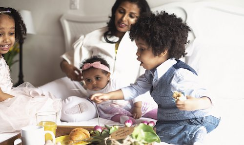 mother with 3 young children in her bed having breakfast served