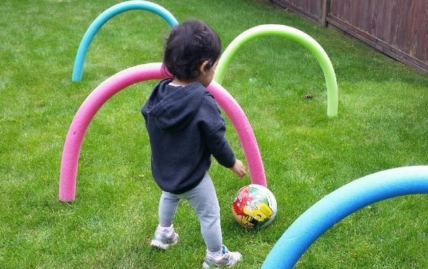 toddler kicking soccer ball around bent pool noodles in an obstacle course