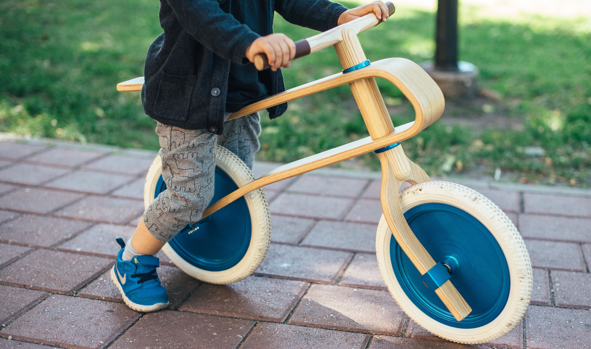 toddler boy with blue jacket standing on a balance bike