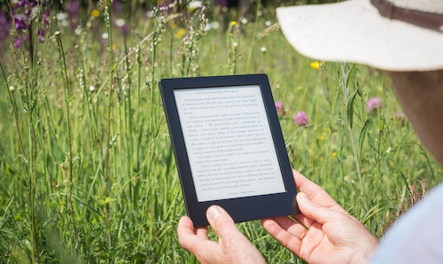 woman reading her e-book in her hands seated in the grass